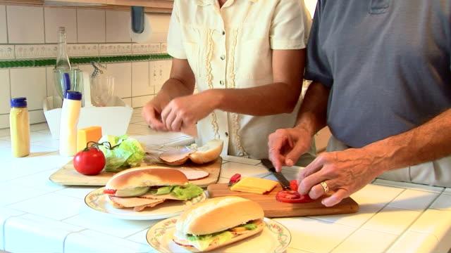 Mature couple making sandwiches