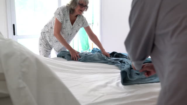 mature couple making the bed together - bed furniture stock videos & royalty-free footage