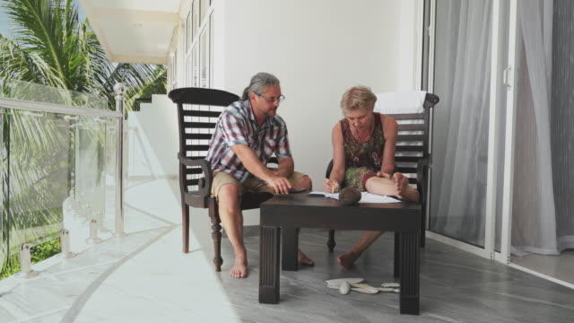 reifes paar, mann und frau arbeiten zusammen auf einem balkon in einem modernen hotel - hotel stock-videos und b-roll-filmmaterial