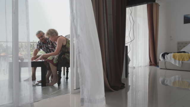 mature couple, man, and woman working together on a balcony in a contemporary hotel - 50 59 years stock videos & royalty-free footage