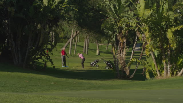 LS mature couple of golfers on fairway, woman plays ball to camera, RED R3D 4K