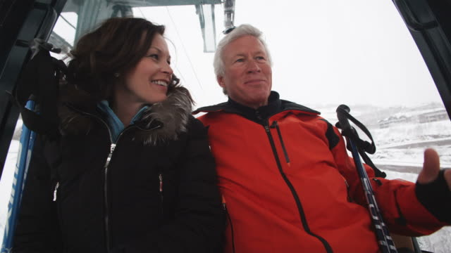 mature couple on a gondola chair lift at a ski resort