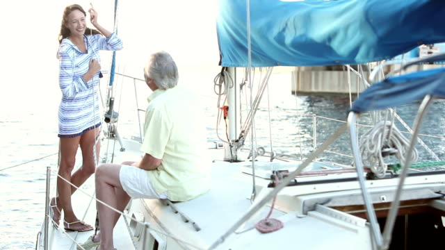 mature couple on deck of sailboat, talking, laughing - marina stock videos & royalty-free footage