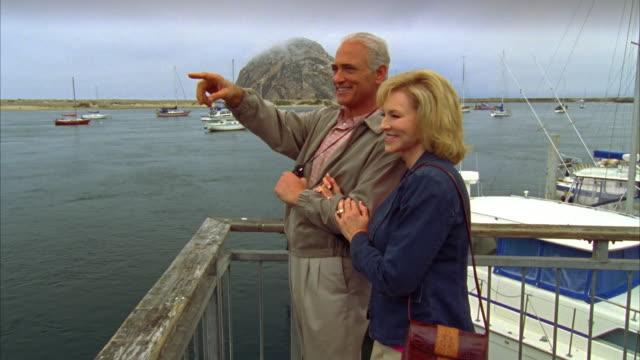 ms, pan, mature couple on pier in morro bay, man looking through binoculars, california, usa - isoliert stock-videos und b-roll-filmmaterial