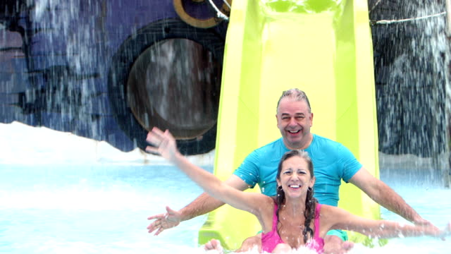 mature couple on water slide, joined by granddaughter - 50 59 years stock videos & royalty-free footage