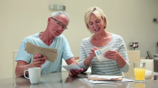 mature couple opning letter and laughing - reading mail stock videos & royalty-free footage