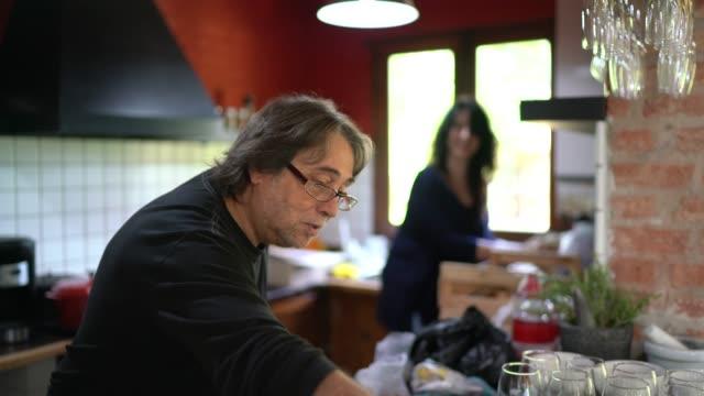 vídeos de stock e filmes b-roll de mature couple organizing and talking in the kitchen - 50 anos