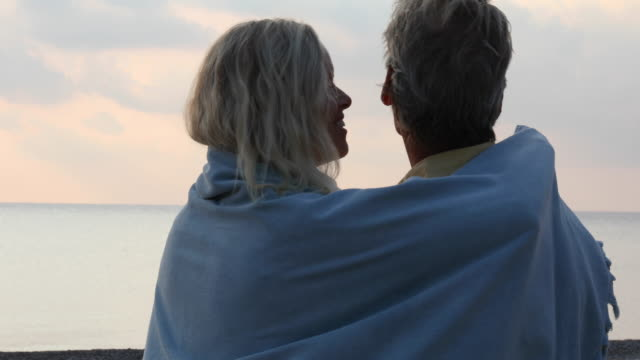 mature couple pause on empty beach at sunrise - blanket stock videos & royalty-free footage