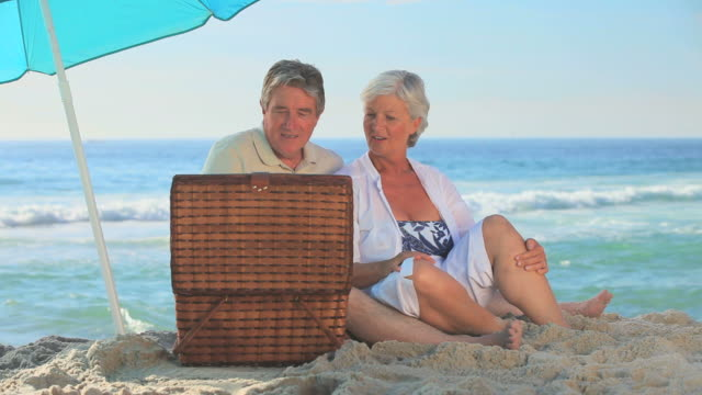 vidéos et rushes de mature couple picnicking on a beach / cape town, western cape, south africa - panier de pique nique