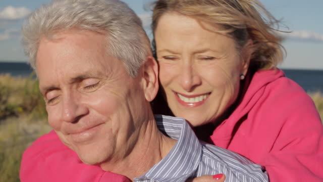 CU Mature couple piggy back ride in beach / Sea Bright, New Jersey, USA