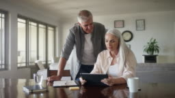 Mature couple planning expenses at home
