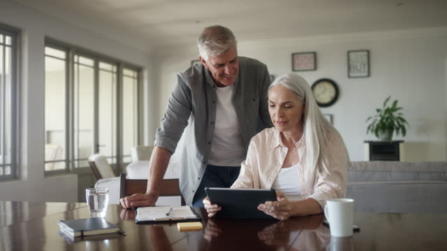 mature couple planning expenses at home - paperwork stock videos & royalty-free footage