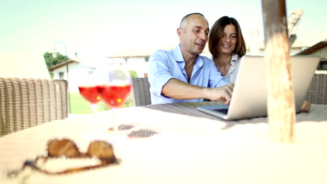 Mature couple planning vacation on laptop