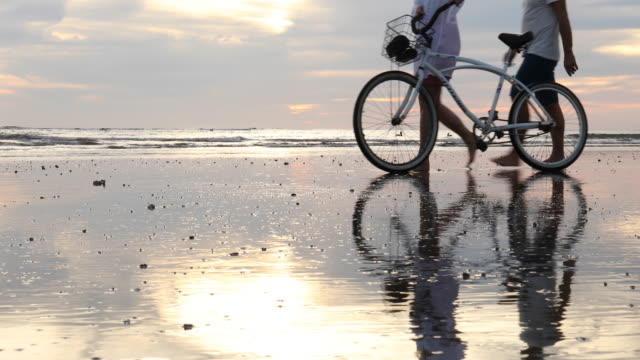 mature couple push bicycle along tidal flat at sunrise - lockdown viewpoint stock videos & royalty-free footage