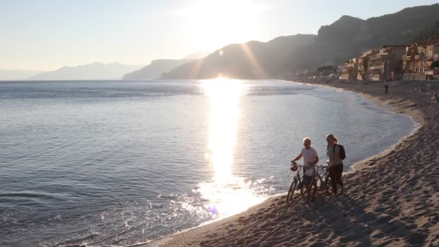 Mature couple push bikes along beach edge, sunrise