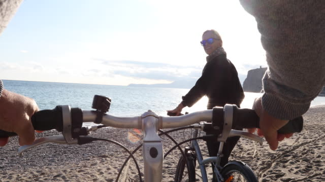 vídeos de stock, filmes e b-roll de casal maturo empurrar as bicicletas ao longo da praia vazia - top