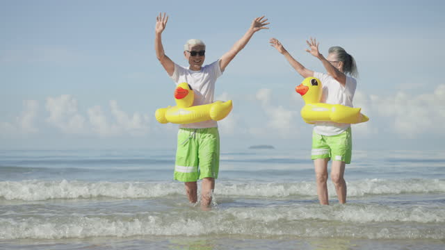 mature couple raises arm with feeling positive emotion, excited in couple cloth, white t-shirt, green shorts at the beach, senior adult with yellow swimming ring running to sea with happiness in holiday summer, looking at camera. - swimming shorts stock videos & royalty-free footage