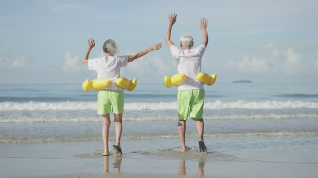 mature couple raises arm with feeling positive emotion, excited in couple cloth, white t-shirt, green shorts at the beach, senior adult with yellow swimming ring running to sea with happiness in holiday summer. - swimming shorts stock videos & royalty-free footage