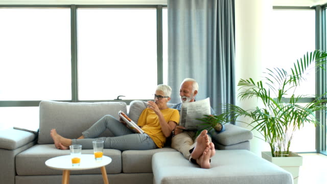 mature couple reading magazines and having a conversation. - living room stock videos & royalty-free footage