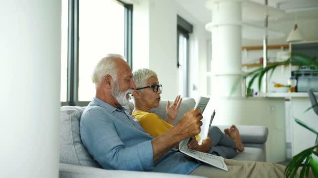vídeos y material grabado en eventos de stock de pareja madura leyendo revistas y teniendo una conversación. - 60 69 años