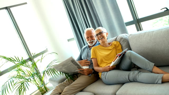 mature couple reading magazines and relaxing. - magazine publication stock videos & royalty-free footage
