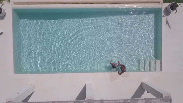 mature couple relax and swim in pool - swimming pool stock videos & royalty-free footage