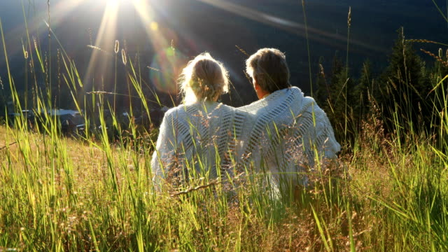 mature couple relax in grasses, look out over mountains - bonding stock videos & royalty-free footage