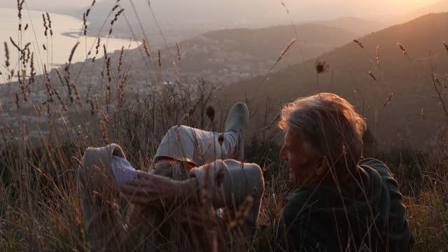 vidéos et rushes de mature couple relax in grassy mountain meadow - activités de week end