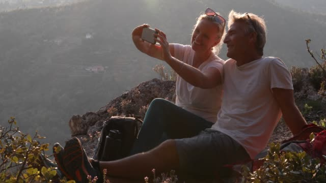 reife ehepaare entspannen sich beim wandern auf der bergwiese - 55 59 jahre stock-videos und b-roll-filmmaterial