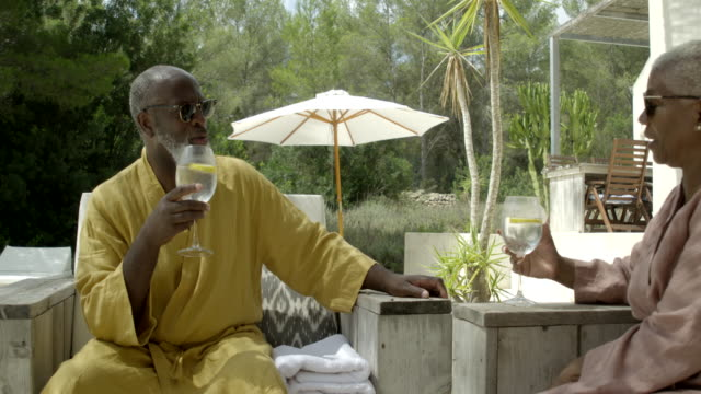 mature couple relax on a sunny terrace - bathrobe stock videos & royalty-free footage
