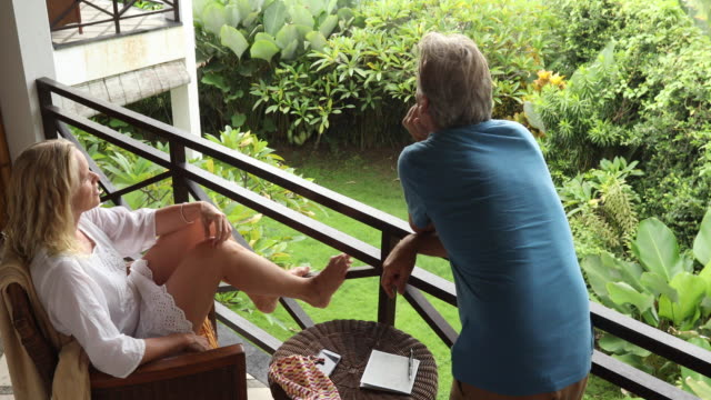 mature couple relax on balcony of holiday villa - holiday villa stock videos & royalty-free footage