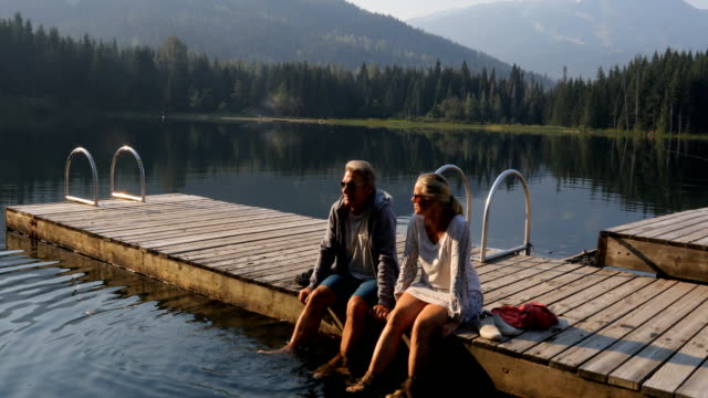 mature couple relax on dock during mountain sunrise - mature adult stock videos & royalty-free footage