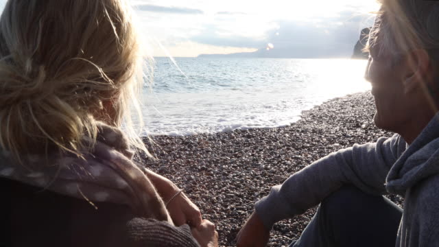 mature couple relax on empty beach, sunrise - grey jacket stock videos and b-roll footage