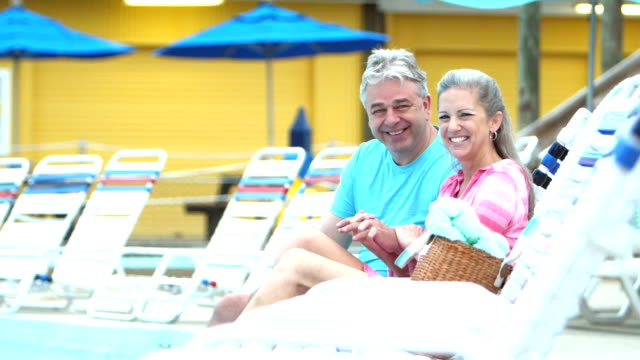 mature couple relaxing by pool, holding hands - mature couple stock videos & royalty-free footage