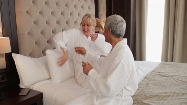 älteres paar entspannende im hotelzimmer - in den fünfzigern stock-videos und b-roll-filmmaterial
