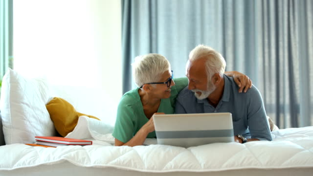 mature couple relaxing on bed and using a laptop. - mature men stock videos & royalty-free footage