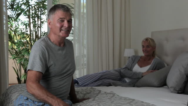 stockvideo's en b-roll-footage met mature couple relaxing on bed - dubbel bed