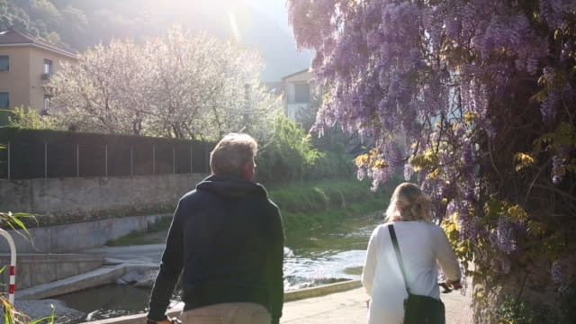 vidéos et rushes de couple mature ride vélos passé glycines fleurs - hommes d'âge mûr