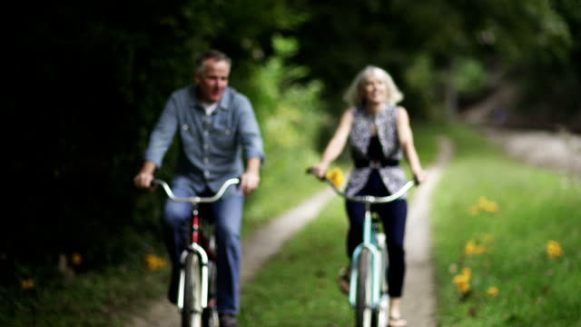 mature couple riding bicycles at park. - mature couple stock videos & royalty-free footage