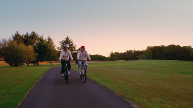 ms, mature couple riding bike in park, front view, usa, pennsylvania, solebury - giovane nell'animo video stock e b–roll
