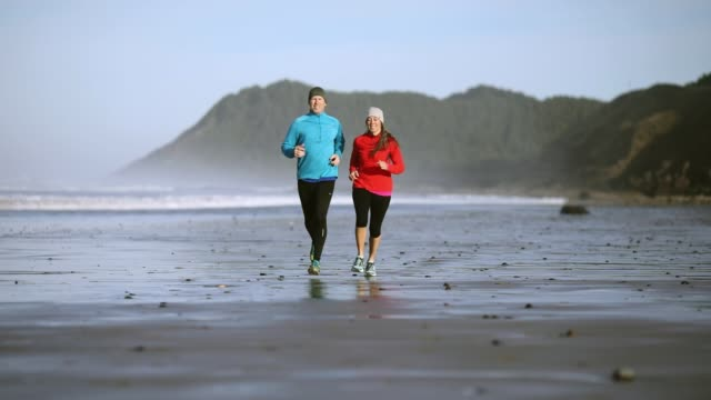 mature couple run on morning oregon coast beach - oregon coast stock videos & royalty-free footage