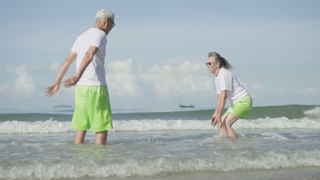 mature couple running to sea with feeling positive emotion, excited in  swimming couple cloth at the beach, retirement senior adult in holiday summer - swimming shorts stock videos & royalty-free footage