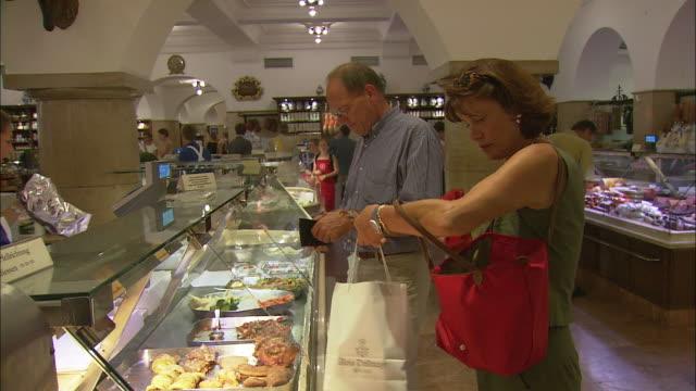 MS PAN Mature couple shopping at Dallmayr, luxury delicatessen, Munich, Bavaria, Germany