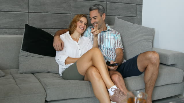 mature couple sitting at home together watching tv - mature couple stock videos & royalty-free footage