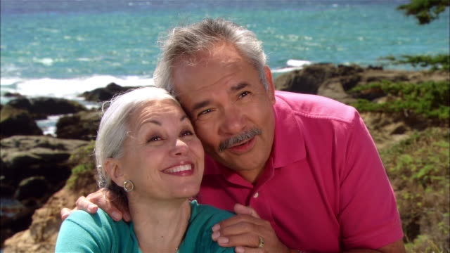 vidéos et rushes de cu, mature couple sitting at seashore, smiling, moonstone beach, cambria, california, usa - 65 69 ans
