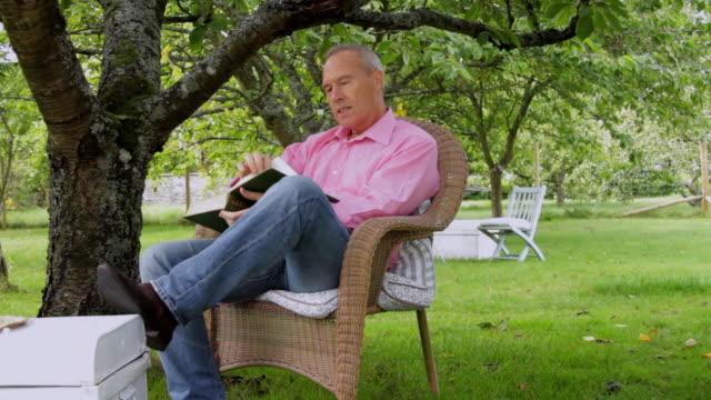ws pan mature couple sitting in garden / london, united kingdom - cinquantenne video stock e b–roll