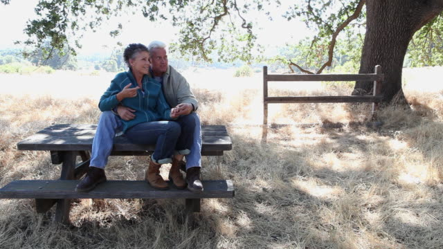 Mature couple sitting on a picnic table