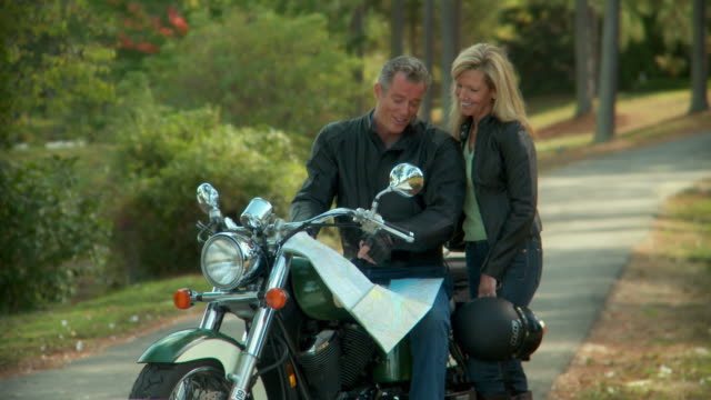 MS, Mature couple sitting on motorcycle and looking at map, Richmond, Virginia, USA