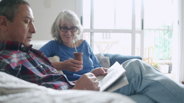 mature couple sitting together on the sofa at home, doing crosswords puzzles. they are talking and drinking yerba mate together. - crossword stock videos & royalty-free footage