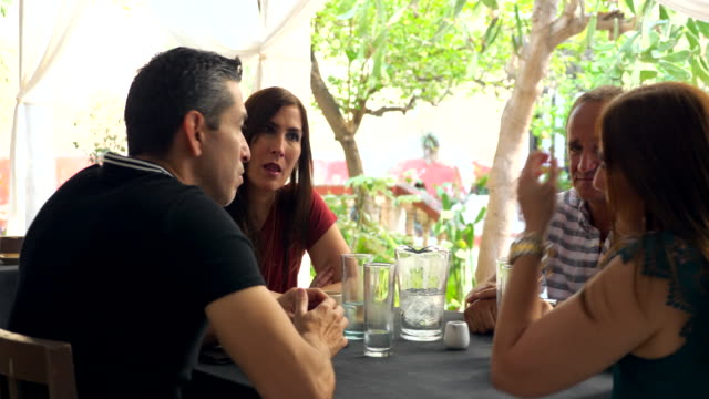 ms mature couple sitting with friends at outdoor cafe at villa while on vacation - real wife sharing stock-videos und b-roll-filmmaterial